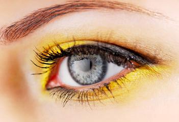 Beauty. Woman eye with yellow eyeshadow.