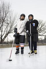 Two boys in ice hockey uniforms holding hockey sticks.