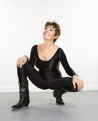 Woman in spandex bodysuit and black cowboy boots smiling.