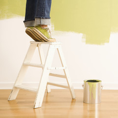 Legs of woman standing on tiptoe on stepladder with paint can.