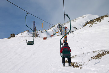 ski lift with skiers in Caucasus mountains
