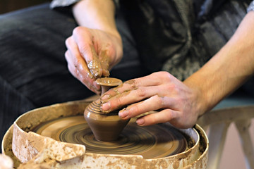 Hands of ceramist with earthenware on potter's lathe