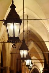 Old stylish lanterns illuminating gothic arcade