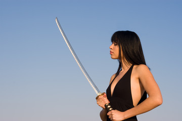 Asian model posing with a sword against blue sky