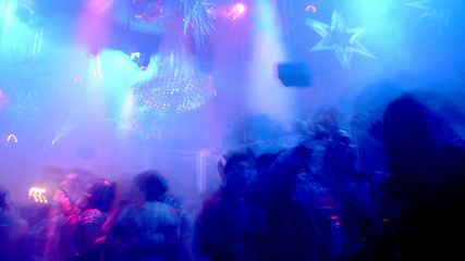 Nightclub scene with christmas decor and dancing crowd in motion