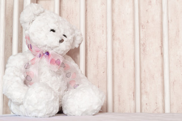 Small, white teddy bear, childish toy sitting at bed