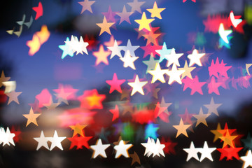 Blurred holiday background with star-shaped highlights.