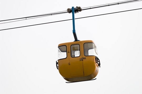 yellow cable car hanging in the sky