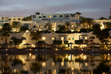 mediterranean hotel on sea coast with reflection in water