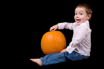 Young boy sitting with a pumpkin