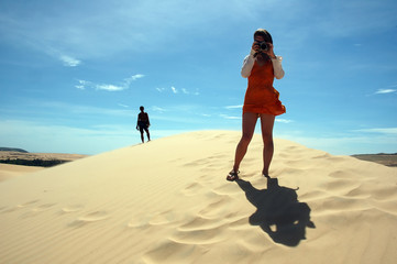 girl taking picture in sand dunes
