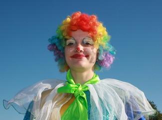 Expressive bizzare clown in colored wig upon blue sky