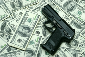 Black gun on 100-bucks background. Clos-Up studio shot.