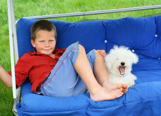 A blond smiling boy and a yawning puppy relaxing