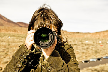 Brown haired woman taking picture.