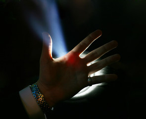 Man's hand on a background of a blue beam
