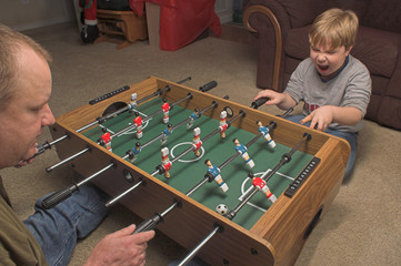 A man and a boy playing a game of foosball.