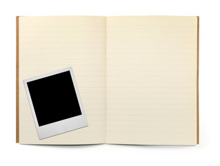 lined exercise book and photo frame on white,