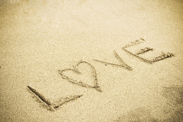 A drawing of letter LOVE on the sandy beach