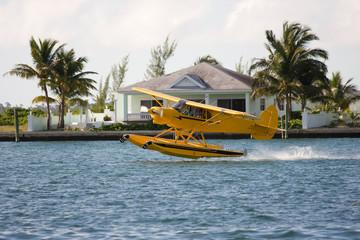 small yellow seaplane taking off close to shore