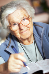 Elderly woman solving crossword puzzle