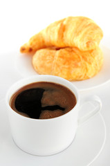Breaksfast of black coffee and fresh croissants