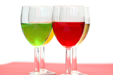 Glasses with drinks of various colours on white