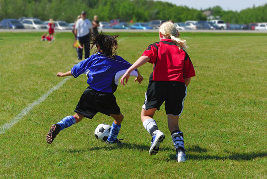 Two youth soccer players in action