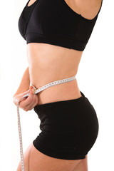 Middle aged lady in her late thirties measuring her waist