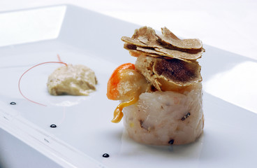 Rolled fish fillet and shell meat with truffle slices on top