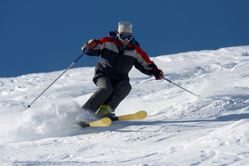 freeride skiing in powder snow against blue sky