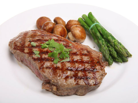 Rare sirloin steak with asparagus tips and sauteed mushrooms