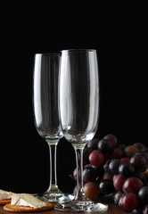 Two empty wine flutes with brie cheese and crackers