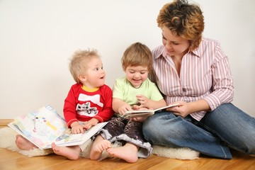 children looking books with mother