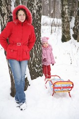 mother and child stand in park at winter