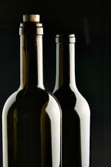 Necks of two bottles over black background