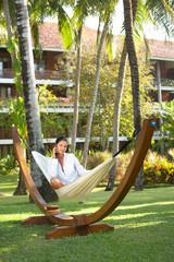 woman portrait ralaxing on hammock at exotic surrounding