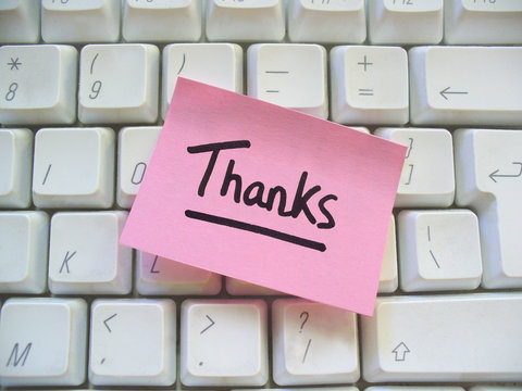 message of thanks post-it note on a computer keyboard