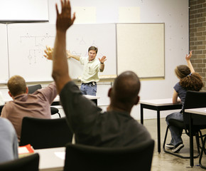 Adult education class raising hands to ask questions.
