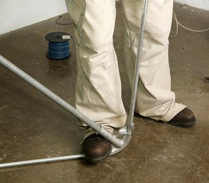 Closeup of electrician's feet as he bends pipe.