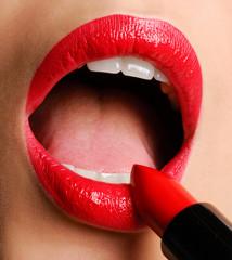 Female applying red lipstick
