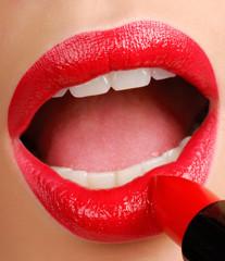 Beauty - Woman applying red lipstick.