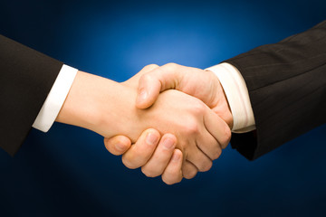 Business handshake - making a deal over blue background