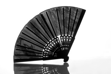 Silhouette of open black fan with reflection