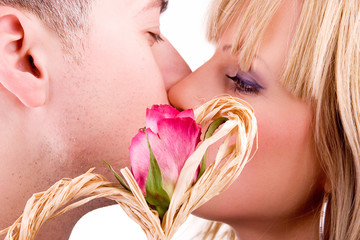 young couple in love kissing behind red rose (isolated on white)