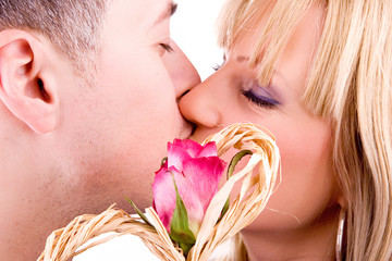 young couple in love kissing, (focus on rose), isolated on white