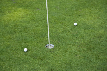 Golf hole on a green with two balls