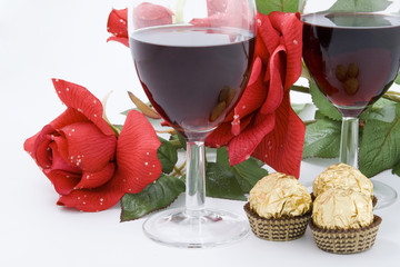 Red Rose, candies and two glasses of wine
