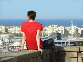 young man and a panorama of Barcelona
