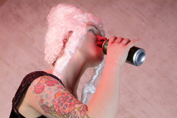 woman with white peruke and tattooed , drinks from the can